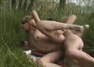 Shades-wearing blonde rides dad's cock in the woods